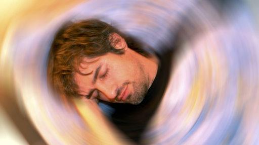 Ein Mann schläft, um ihn herum unscharfe Kreise (Symbolbild)