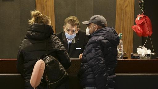 Zwei Gäste checken in einem Hotel ein und tragen wegen der Corona-Pandemie Masken.