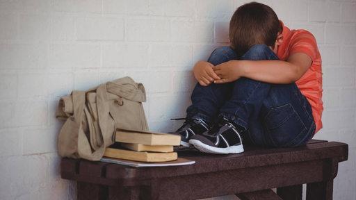 Ein Junge sitzt traurig auf einem Tisch, den Kopf auf die Knie gelehnt.
