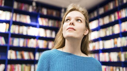 Eine junge Frau sieht sich in einer Bibliothek um.