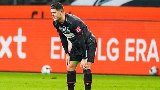 Milot Rashica stützt sich auf dem Spielfeld mit den Händen auf seinen Oberschenkeln ab und schaut zerknirscht.