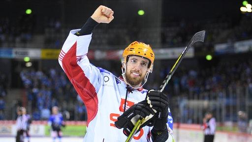 Eishockey-Profi Christian Hilbrich reckt auf dem Eis jubelnd die Faust empor und lächelt.