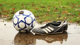 Ein Ball liegt vor zwei Fußballschuhen im Matsch.