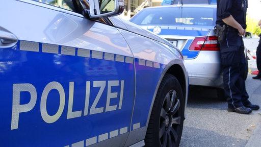 Ein Polizeiauto steht an einer Straße, im Hintergrund ist ein Polizist zu sehen