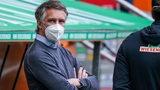Werder-Sportchef Frank Baumann steht nachdenklich mit verschränkten Armen und weißer FFP2-Maske nach dem Spiel in Augsburg am Spielfeldrand.