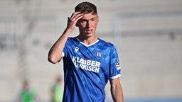 Werders Leihspieler Benjamin Goller fasst sich im Spiel für Karlsruhe nachdenklich an den Kopf.