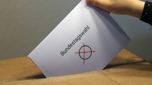 Ein Umschlag wird in eine Wahlurne gesteckt.