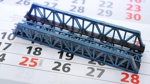 Eine Modellbrücke liegt auf einem Kalender.