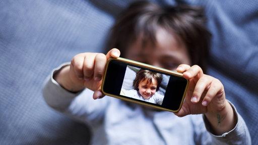 Ein Kind liegt auf einem Sofa und hält ein Smartphone vor sein Gesicht. Auf dem Bildschirm des Handy ist das Gesicht des Kindes zu sehen.