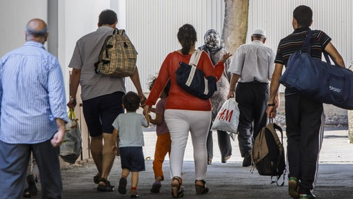 Flüchtlingsfamilie mit Taschen und Koffern.