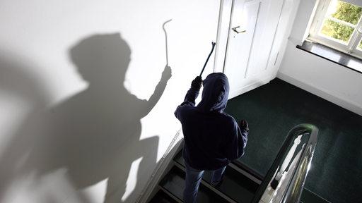 Eine vermummte Person geht mit Brechstange auf eine Tür zu.
