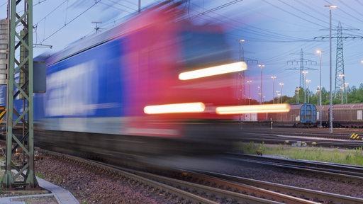 Ein Güterzug fährt abends auf einem Rangierbahnhof vorbei
