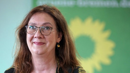 Karoline Linnert vor einem Plakat der Grünen.