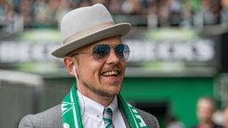 Jan Delay im grauen Anzug, mit Hut, Sonnenbrille und Werder-Schal im Weser-Stadion.