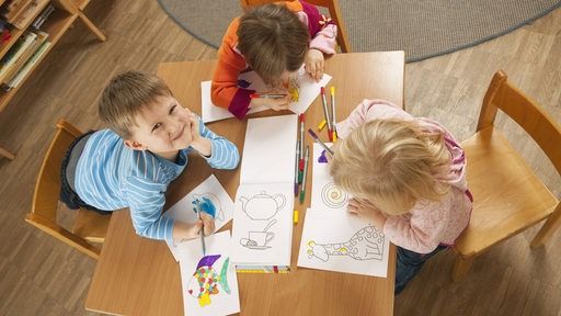 Kinder in einer Kindertagesstätte arbeiten an einem Tisch (Symbolfoto)