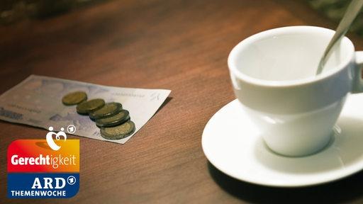 Neben einer leeren Kaffeetasse liegt Geld auf dem Tisch.