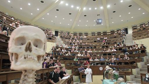 Studenten in einem Hörsaal mit Skelett
