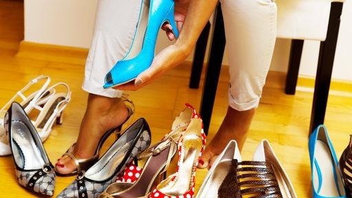 Eine junge Frau hat viele verschiedene Schuhe zur Auswahl.