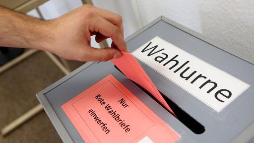Eine Hand wirft einen Umschlag in eine Wahlurne.
