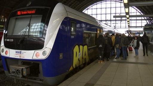 Menschen steigen am Hauptbahnhof Bremen in einen zug der Nordwestbahn