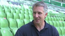 Frank Baumann sitzt auf der Tribüne des Weser-Stadions und lächelt in die Kamera.