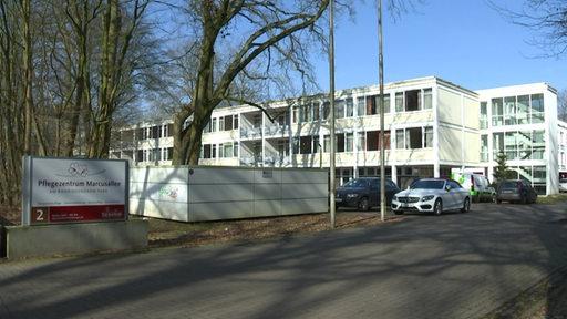 Ein weißes Gebäude, welches als Pflegeheim genutzt wird. Es ist das Pflegezentrum Marcusallee. Vor dem Gebäude stehen Autos auf dem Parkplatz.