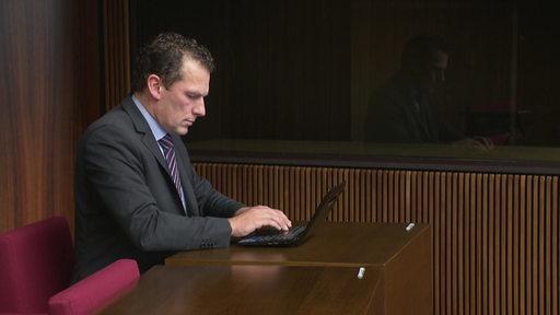 Politiker Jan Timke sitzt im Anzug an einem Laptop.