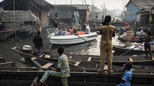 Ein Boot mit Ausflüglern fährt auf dem Kanal im Slum der nigerianischen Stadt Lagos.