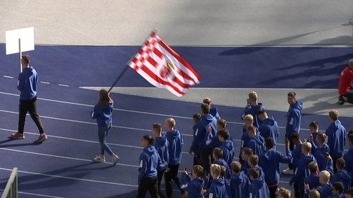 Eine Gruppe von Jugendlichen wird von einer Fahnenträgerin mit Bremer Speckflagge angeführt.