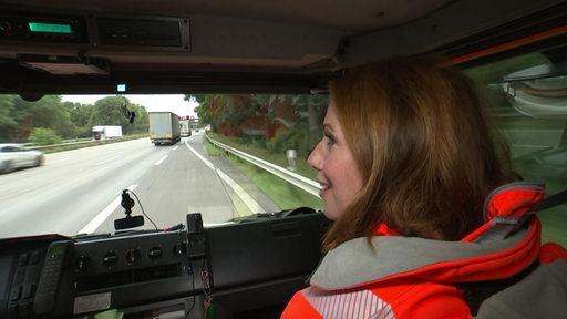 Reporterin Katja Runge sitzt in einem Auto, das gerade auf die Autobahn fährt.