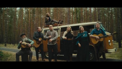 Mitglieder der Kelly Family singen vor einem VW-Bus.