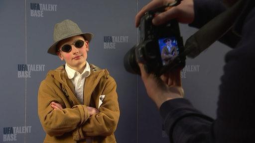 Ein Kind posiert mit Hut und Sonnenbrille bei einem Kindercasting von der Kamera.