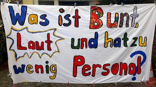 """Banner der Initiative """"Kitanotstand Bremen"""": Was ist Bunt, Laut und hat zu wenig Personal?"""