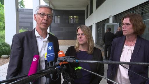 Carsten Sieling, Maike Schäfer und Kristina Vogt sprechen mit der Presse, vor ihnen sind mehrere Mikrofone zu sehen.