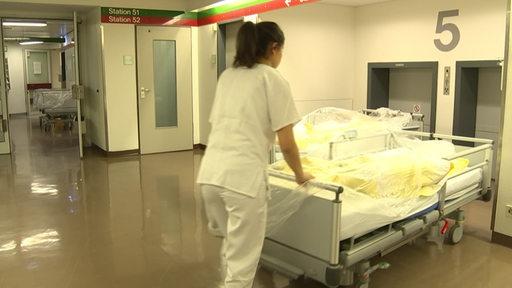 Eine Pflegekraft schiebt ein Bett in einem Krankenhaus.