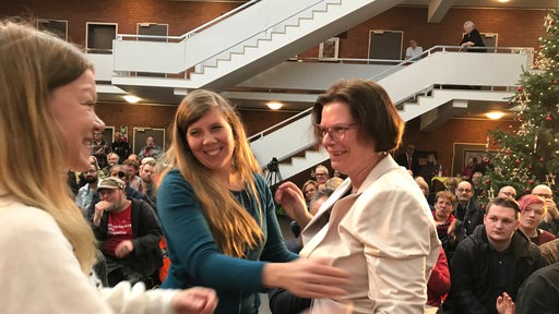 Kristina Vogt von der Linken wird von zwei Parteikolleginnen in den Arm genommen.