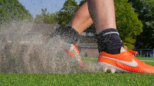 Zwei Füße mit Fussballschuhen wirbeln Granulat auf einem Kunstrasen auf.