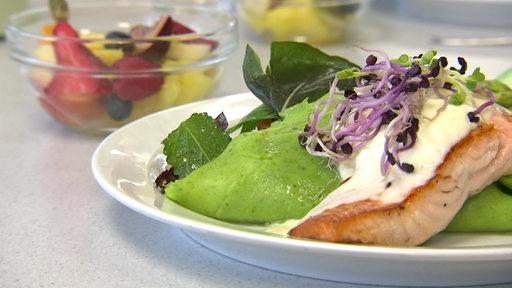 Ein Teller auf dem Lachs mit grünen Pfannkuchen angerichtet ist. Im Hintergrund eine kleine Schale mit zugeschnittenem Obst.
