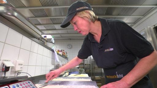 Reporterin Anke Kültur beim Bestreichen der Teigwaren in der Küche.