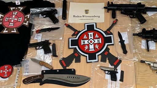 Diverse Waffen und Symbole des Ku-Klux-Klans liegen auf einem Tisch