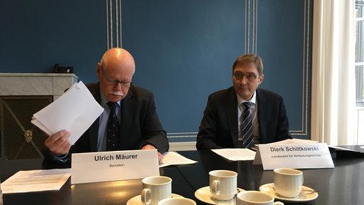 Innensenator Ulrich Mäurer und Verfassungsschutzchef Dierk Schittkowski sitzen an einem Tisch.