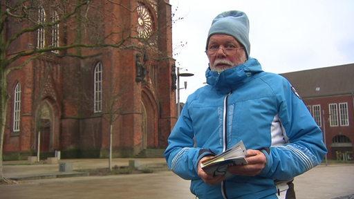 Der Autor Hervé Maillet steht vor einer Kirche. In seinen Händen hält er ein Buch.