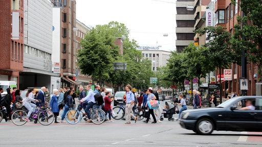 Viele Menschen gehen an einer Ampel über die Martinistraße am Brill.