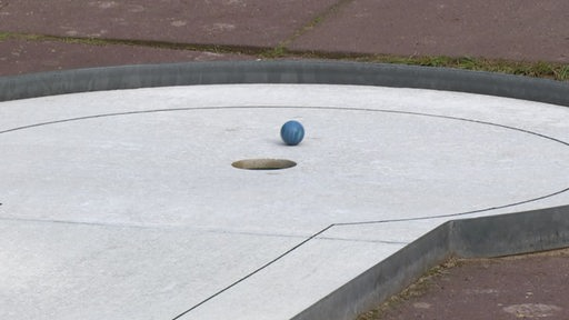 Ein Minigolfball rollt ins Loch