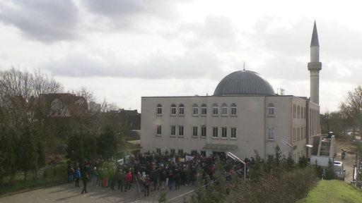 Luftaufnahme einer Moschee, vor der eine große Gruppe von Personen steht.