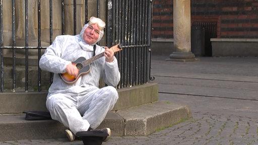 Ein Mann sitzt mit einem Schutzanzug bekleidet und einer Schutzbrille auf dem Kopf auf dem Boden und spielt Ukulele.