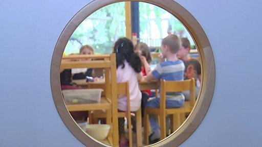 Durch ein Lukenfenster sind einige Kinder in einer Kita zu sehen