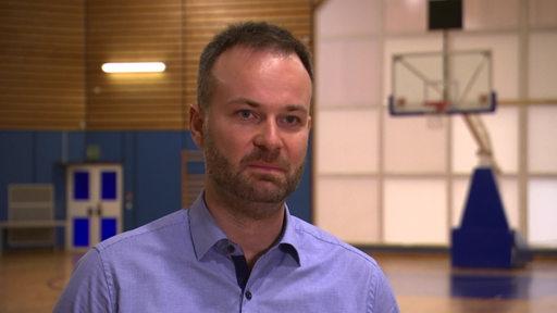 Ein Mann mit blauem Hemd im Interview. Im Hintergrund ein Basketballkorb.