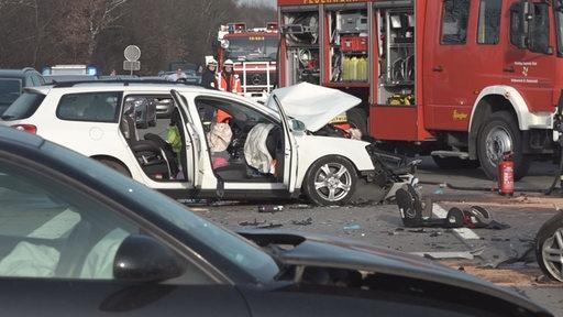Ein Unfallwagen steht auf einer Straße, daneben ein Feuerwehrauto