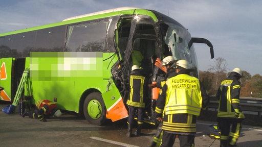 Feuerwehrleute stehen vor einem Reisebus auf einer Autobahn.